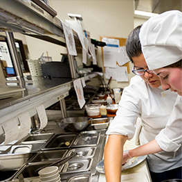 Culinary arts student working with instructor