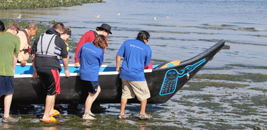 Students and community members launching a canoe on the beach