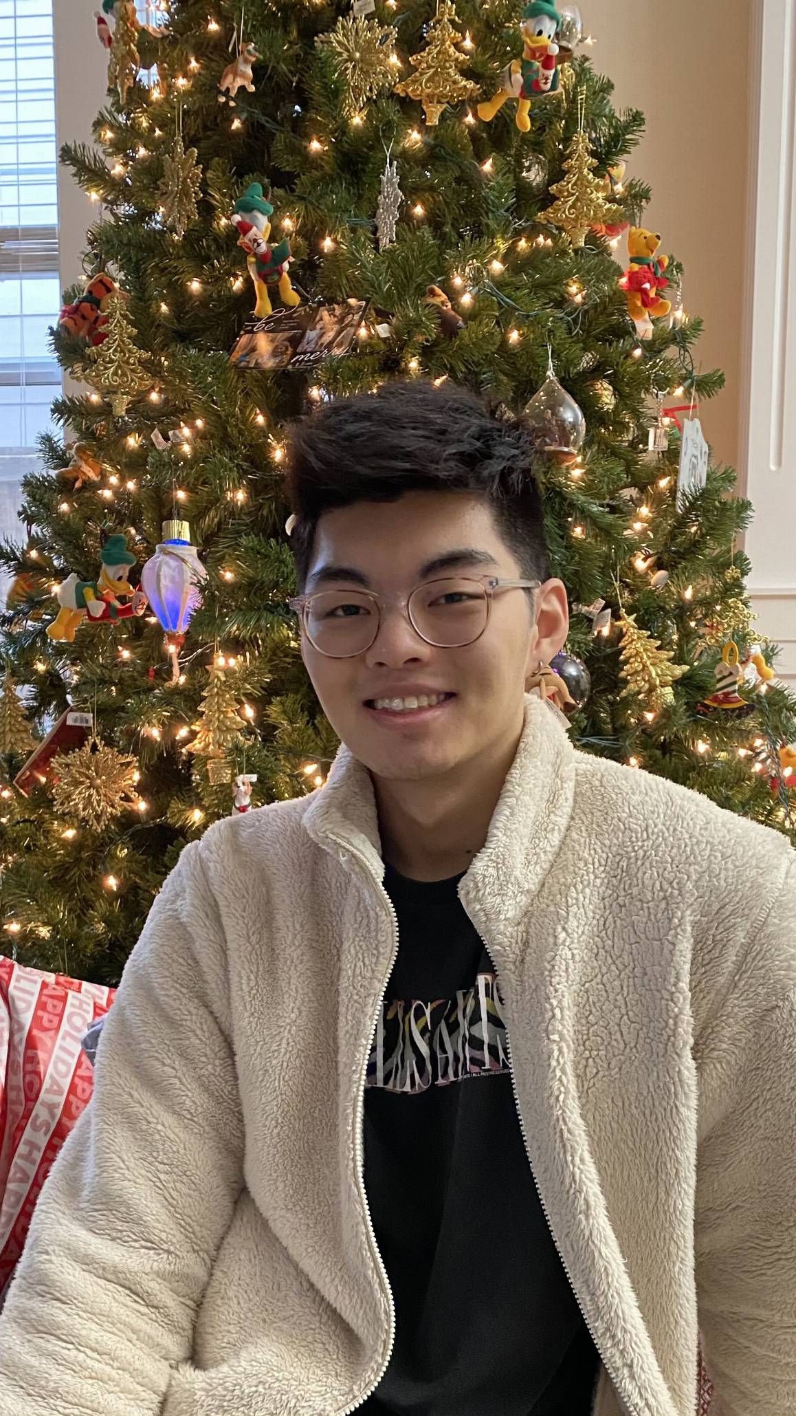 Eric Chung in front of a Christmas tree. He