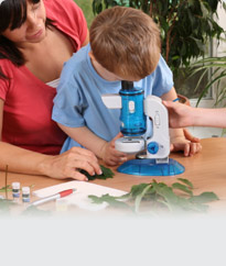 Child and teacher looking through microscope