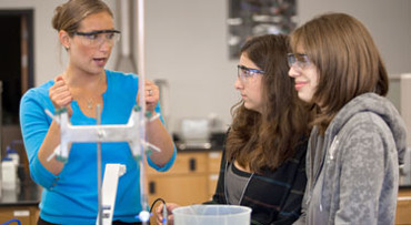 female students with a teacher in the chemistry lab
