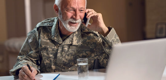 Man using a laptop and talking on the phone