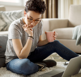 woman using a laptop and sitting on the floor