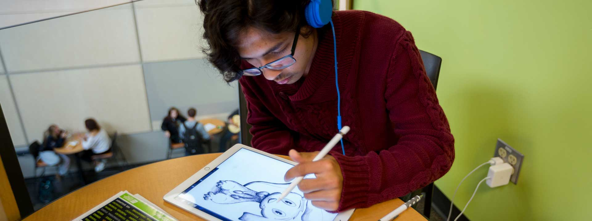 Student drawing on a tablet