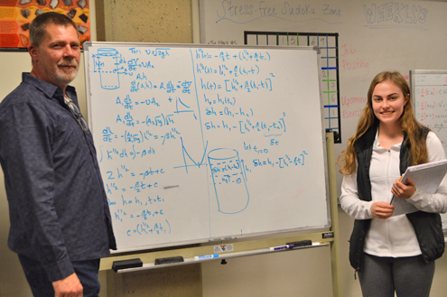 Student and teacher looking at white board with math