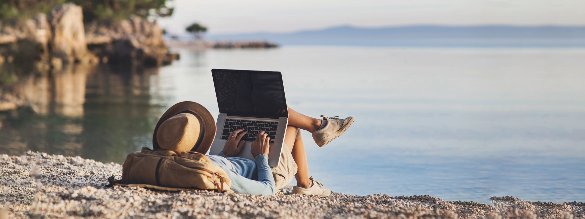 woman using a laptop on the beach