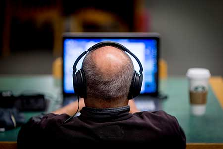 man wearing headphones looking at a computer